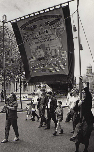 Lynda Walker & Ann Hope carry Belfast Trades Council Banner, May Day, 1980s. (Image reproduced with kind permission of Lynda Walker).